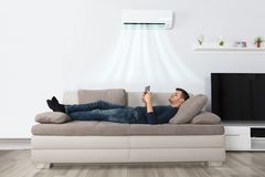 Man Lying On Couch Under Air Conditioner Using Tablet. Young Man Lying Under Air Conditioner On Couch Using Tablet At Home stock images