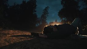 Man lying on country road lighted by car headlight after accident. Man lying on country road lighted by car steamy headlight after accident on summer night stock video