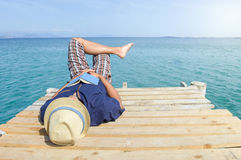 Man lying on the dock with a book Stock Image