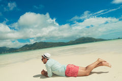 Man lying down contemplating the exotic view. Young man lying down in sand contemplating the exotic view Royalty Free Stock Photography