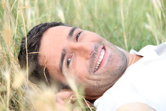 Man lying down in a field Stock Photography