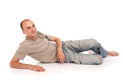Man lying down on a floor. Happy young man lying down on a floor Stock Photography