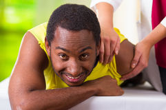 Man lying down getting physical shoulder treatment from physio therapist, patient looking into camera while her hands Stock Photography