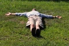 Man lying down like a cross Stock Photo