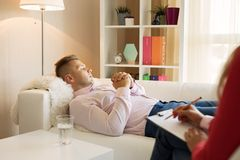 Man lying down in psychologist office royalty free stock photo