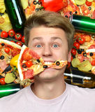 Man lying down with slice of pizza in mouth Stock Photos