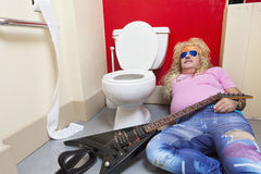 Man lying down in toilet with a guitar Royalty Free Stock Photography