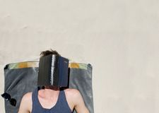 Man lying down on a towel at the beach with book covering face Royalty Free Stock Photos