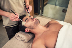 Man lying down during traditional facial treatment at beauty cen Stock Image