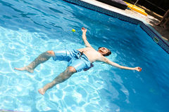 A man lying face up on a pool of clear water Stock Image