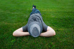 Man lying in a field on green grass with the hat over his face Royalty Free Stock Image