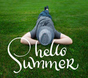 Man lying in a field on green grass with the hat over his face and text Hello summer. Calligraphy lettering hand draw Stock Photo