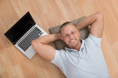 Man Lying On Floor With Laptop Stock Image