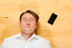 Man lying on the floor beside mobile phone Stock Photography