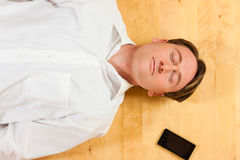Man lying on the floor beside mobile phone Stock Images