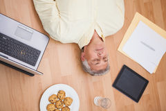 Man lying on floor surrounded by various objects Stock Photography