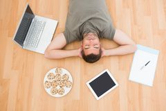 Man lying on floor surrounded by various objects at home Stock Image