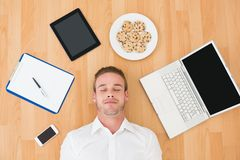 Man lying on floor surrounded by various objects at home Royalty Free Stock Photo
