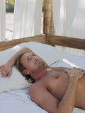 Man Lying In Four-Poster Bed Stock Images