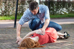 Man lying girl in recovery position Stock Images