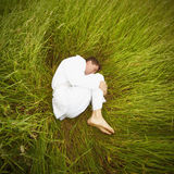 Man lying on grass in fetal position Royalty Free Stock Photography