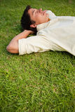 Man lying in grass with his eyes closed Royalty Free Stock Images
