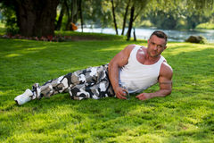 Man Lying On Grass And Holding Bottle Of Water Stock Photo