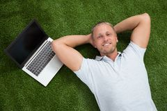 Man Lying On Grass With Laptop Stock Photography