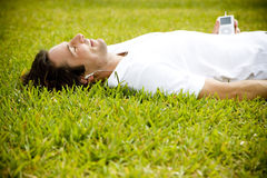 Man lying on the grass listening to music Royalty Free Stock Image