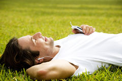 Man lying on the grass listening to personal stereo Royalty Free Stock Photography