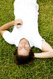 Man lying on the grass listening to personal stereo stock image