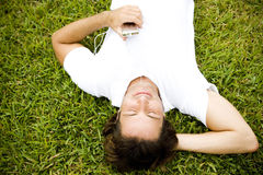 Man lying on the grass listening to personal stereo Stock Photo