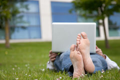 Man lying on the grass looking in the laptop Royalty Free Stock Photo