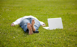 Man lying on the grass looking in the laptop Stock Photo