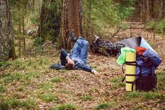 Man lying on grass near his backpack in a forest. A person rests after a long journey. Consolidated way of life and recreation in Royalty Free Stock Photo