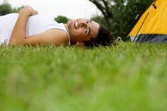 Man lying on grass near tent Royalty Free Stock Photos