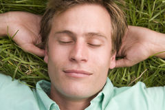 Man lying on grass sleeping Stock Photos