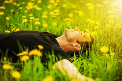 Man lying on grass at sunny day Royalty Free Stock Images
