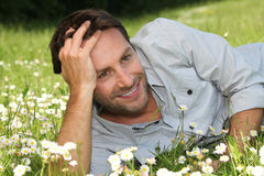 Man lying on grass Stock Images