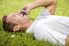 Man lying on the grass talking on mobile phone Stock Photography