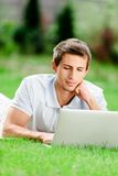 Man lying on the grass works at the computer Stock Photo
