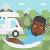 Man lying in hammock in front of motor home. Stock Photography