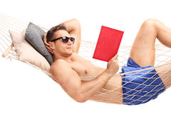 Man lying in a hammock and reading a book Stock Image