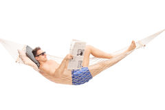 Man lying in a hammock and reading a newspaper Royalty Free Stock Image