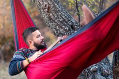 Man lying in a hammock and relaxing outdoors stock images