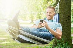 Man Lying In Hammock Using Mobile Phone Stock Photo