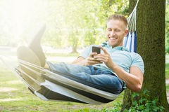 Man Lying In Hammock Using Mobile Phone. Young Happy Man Using Mobile Phone While Relaxing In Hammock At Garden Stock Photo