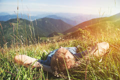 Man lying in high green grass on the mountain medaow Stock Photography