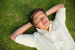 Man lying with his eyes closed and both hands behind his neck. Man lying on the grass with his eyes closed and both hands resting behind his neck Royalty Free Stock Image