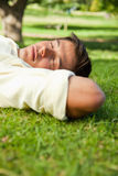 Man lying with his eyes closed and the side of his head resting. Man lying in grass with his eyes closed and his hands resting underneath the side of his head royalty free stock images